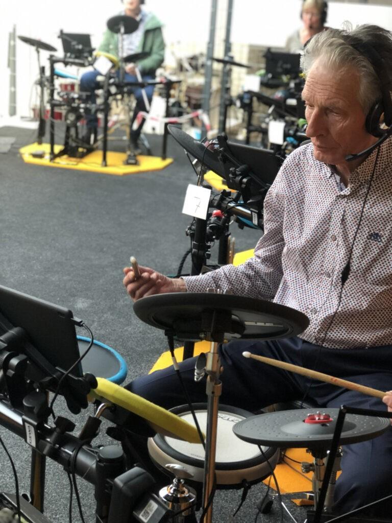oude man achter elektrisch drumstel